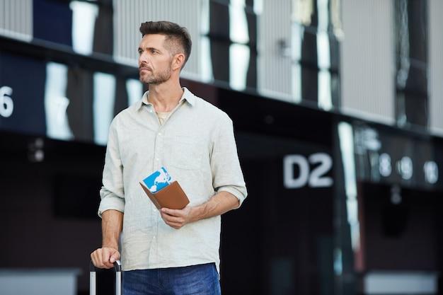 Młody człowiek z biletami i bagażem czekając na swój lot udaje się w podróż służbową