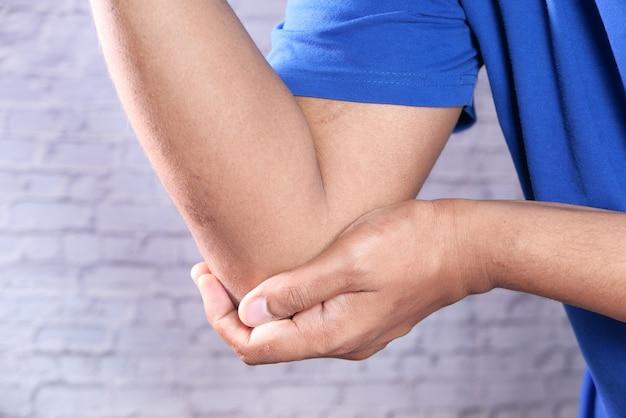 Młody człowiek z bólem łokcia, koncepcja łagodzenia bólu.