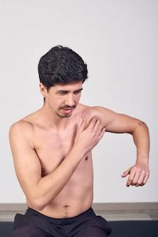 Młody człowiek z bólem w ramieniu w klinice