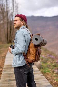 Młody człowiek z brązowym plecakiem odkrywania przyrody na wiosnę, spacerując samotnie na świeżym powietrzu. turystka w swobodnym stroju podróżująca po lasach. krajobrazy wiejskie, góry. widok z tyłu