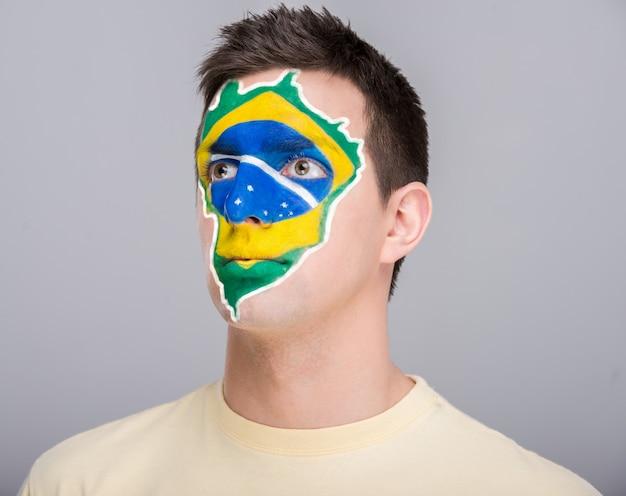 Młody człowiek z brazylijską flaga malującą na jego twarzy.