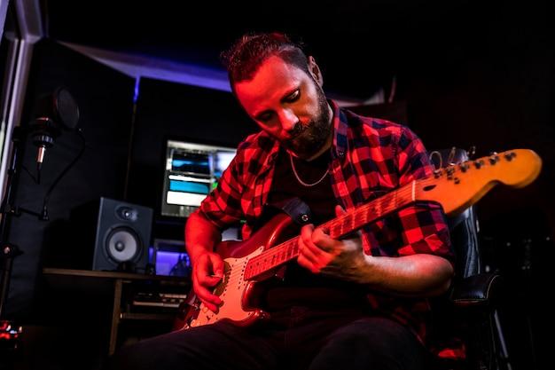 Młody człowiek z brodą gra na gitarze w studiu stereo w radiu, aby nagrać swoją nową piosenkę.