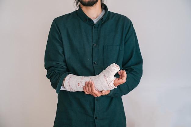 Młody człowiek z brodą i koszulką, trzymając obandażowaną rękę