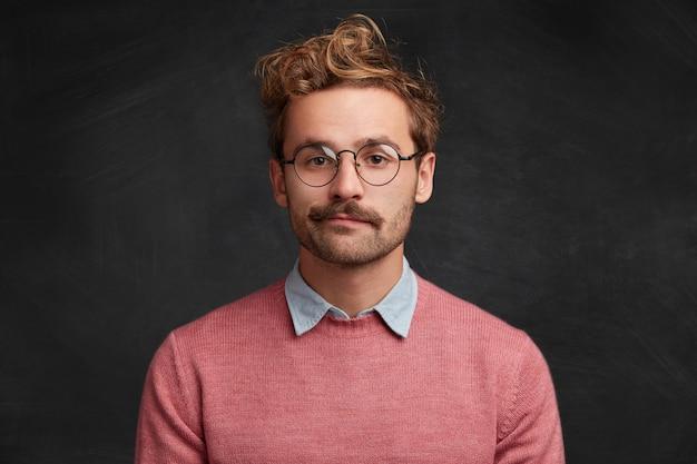 Młody człowiek z brodą i okrągłymi okularami