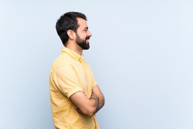 Młody człowiek z brodą na białym tle niebieski w pozycji bocznej