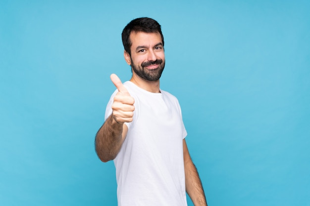 Młody człowiek z brodą na białym tle z kciuki do góry, ponieważ stało się coś dobrego