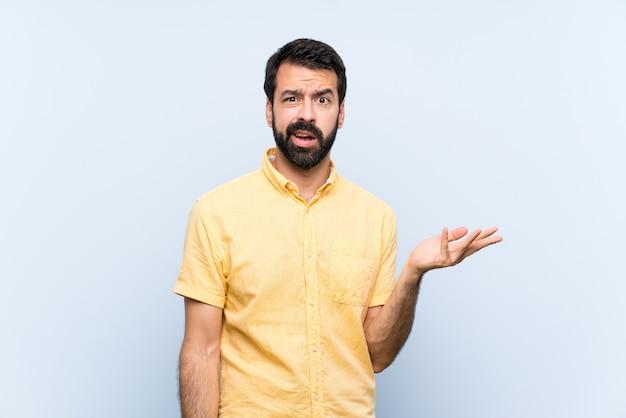 Młody człowiek z brodą na błękicie robi wątpliwość gestowi