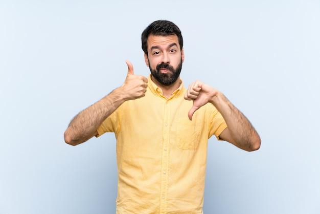 Młody człowiek z brodą na niebiesko robi dobry zły znak. niezdecydowany między tak lub nie