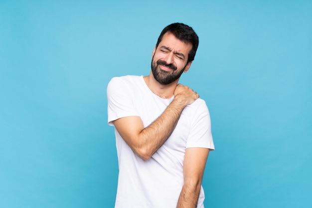 Młody człowiek z brodą na pojedyncze niebieskie cierpienie z bólu w ramieniu za to, że podjął wysiłek