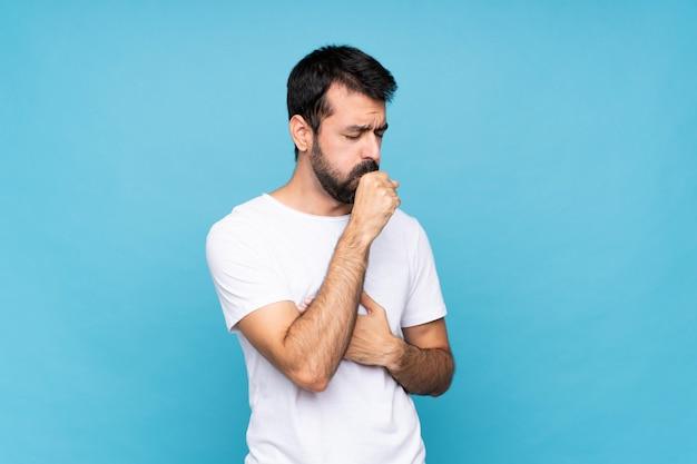Młody człowiek z brodą na pojedyncze niebieskie ściany cierpi na kaszel i źle się czuje