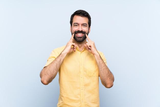 Młody człowiek z brodą na pojedyncze niebieskie ściany, uśmiechając się z wyrażeniem szczęśliwy i przyjemny