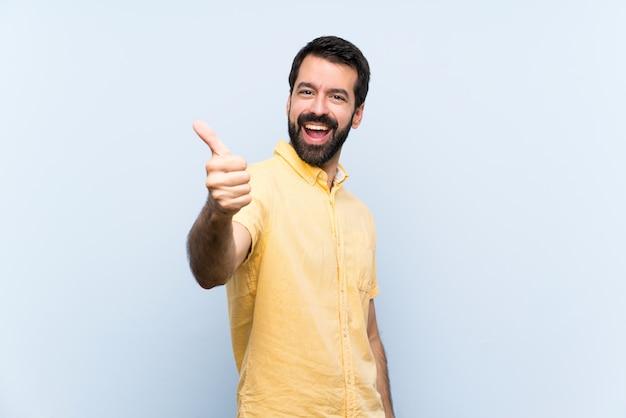 Młody człowiek z brodą na pojedyncze niebieskie ściany z kciuki do góry, ponieważ stało się coś dobrego
