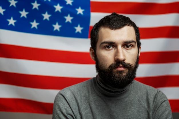 Młody człowiek z brodą na tle flagi amerykańskiej. zbliżenie. dzień niepodległości. zamieszki i wojna domowa.