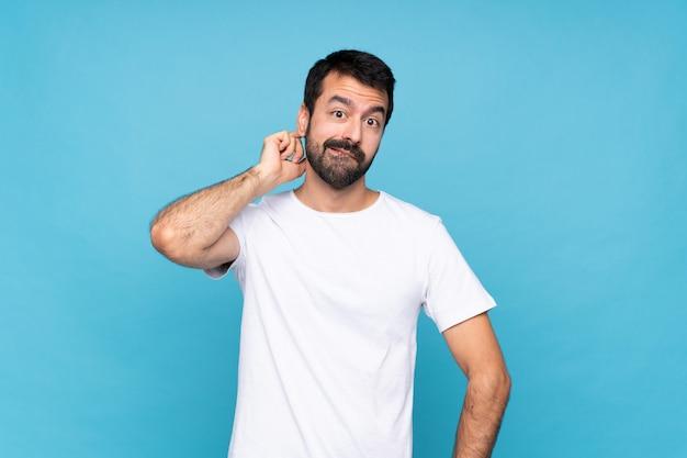 Młody człowiek z brodą nad odosobnioną błękit ścianą ma wątpliwości