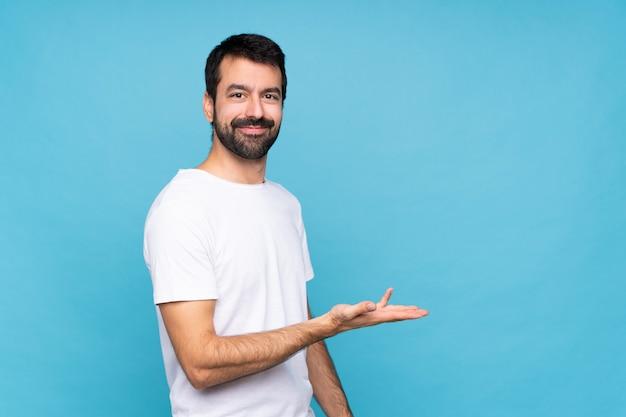 Młody człowiek z brodą nad odosobnioną błękit ścianą przedstawia pomysł podczas gdy patrzejący ono uśmiecha się w kierunku