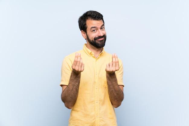 Młody człowiek z brodą nad odosobnioną błękit ścianą robi pieniądze gestowi