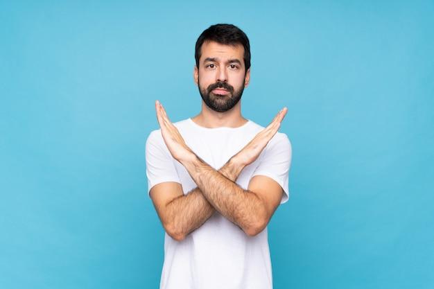 Młody człowiek z brodą nad odosobnioną błękit ścianą robi żadnemu gestowi