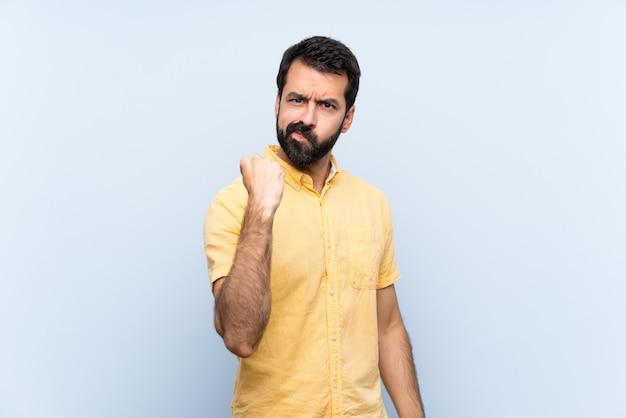 Młody człowiek z brodą nad odosobnioną błękit ścianą z gniewnym gestem