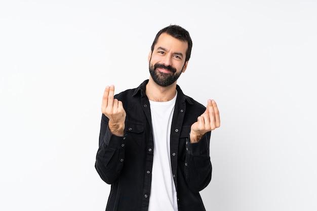 Młody człowiek z brodą nad odosobnionym białym robi pieniądze gestowi