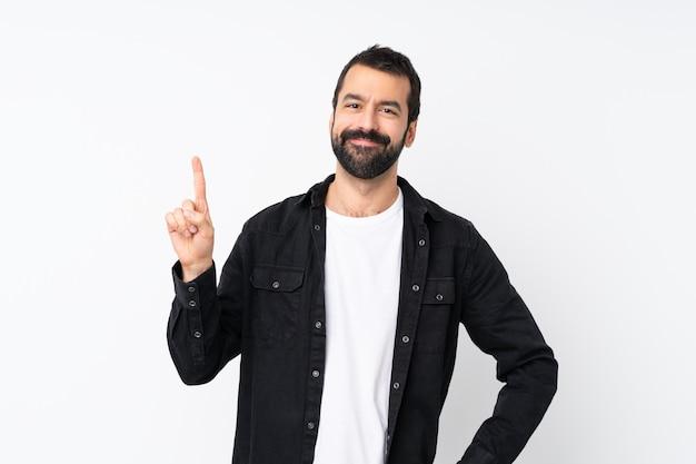 Młody człowiek z brodą nad odosobnionym bielem pokazuje i podnosi palec w znaku najlepszy
