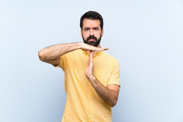 Młody człowiek z brodą nad odosobnionym robi czasowi out gestykuluje