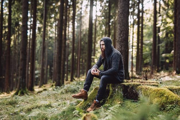 Młody człowiek z brodą siedzi i myśli w lesie