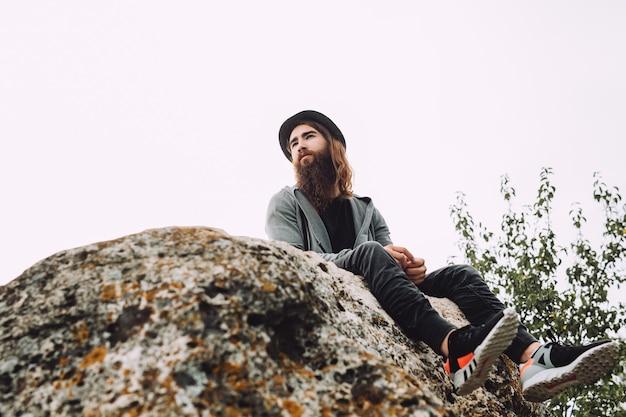 Młody człowiek z brodą siedzi na skale i patrzy na naturę z wysokości.