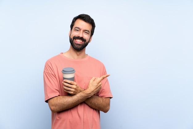 Młody człowiek z brodą trzyma kawę na wynos na niebiesko, wskazując na bok, aby przedstawić produkt