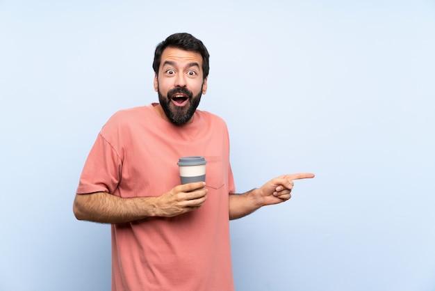Młody człowiek z brodą trzyma kawę na wynos na niebiesko zaskoczony i wskazując palcem na bok