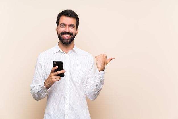 Młody człowiek z brodą trzyma telefon komórkowy wskazując na bok, aby przedstawić produkt