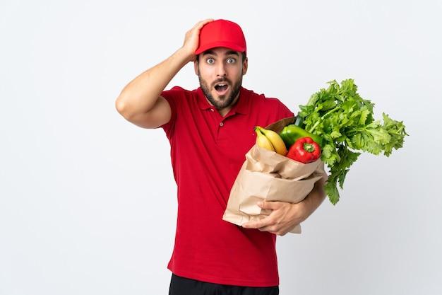 Młody człowiek z brodą, trzymając torbę pełną warzyw na białym tle na białej ścianie z wyrazem twarzy zaskoczenia