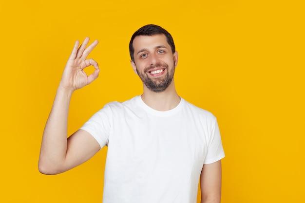 Młody człowiek z brodą w białej koszulce radosna buźka, uśmiechnięty pozytywnie, robi gest ręką i palcami.