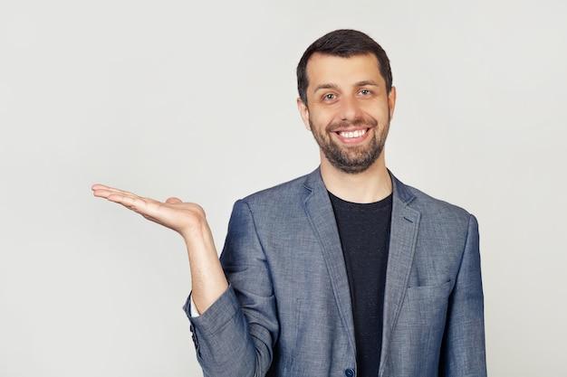 Młody człowiek z brodą w białej koszulce uśmiechnięty, wesoły, prezentujący i wskazujący dłonią