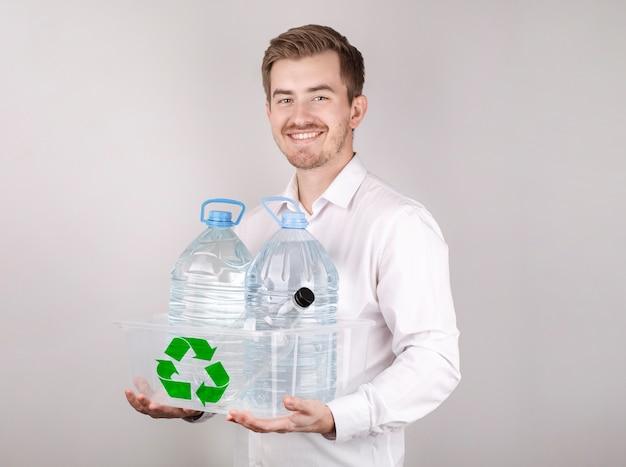 Młody człowiek z brodą w białej koszuli uśmiecha się, przetwarza plastik, zbiera butelki, koncepcja recyklingu
