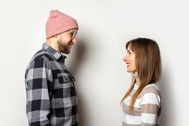 Młody człowiek z brodą w kapeluszu i kraciastej koszuli oraz dziewczyna w swetrze patrzą na siebie na białym tle
