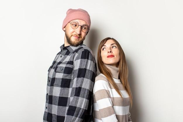 Młody człowiek z brodą w kapeluszu i kraciastej koszuli oraz dziewczyna w swetrze stoją tyłem do siebie i patrzą na siebie