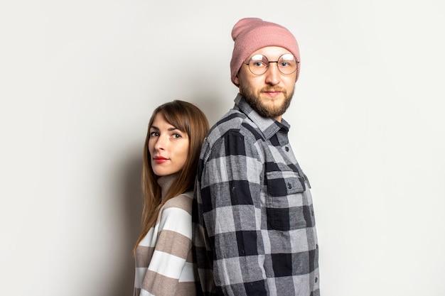Młody człowiek z brodą w kapeluszu i kraciastej koszuli oraz dziewczyna w swetrze stoją tyłem do siebie na odosobnionym jasnym tle.