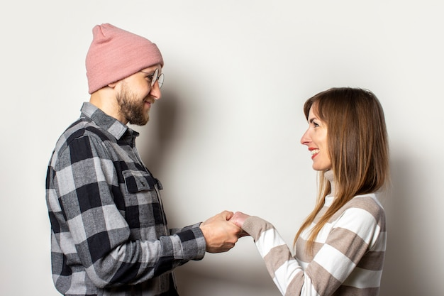 Młody człowiek z brodą w kapeluszu i kraciastej koszuli oraz dziewczyna w swetrze trzymają ręce na odosobnionym świetle