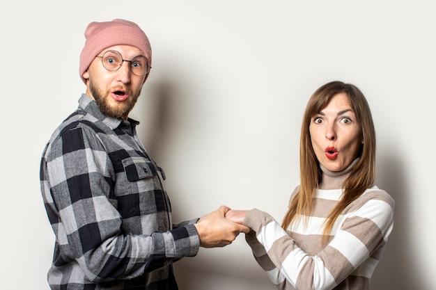 Młody człowiek z brodą w kapeluszu i kraciastej koszuli oraz dziewczyna w swetrze trzymają ręce z zaskoczonymi twarzami na odosobnionym jasnym tle. twarz emocjonalna. szczęśliwa para randki