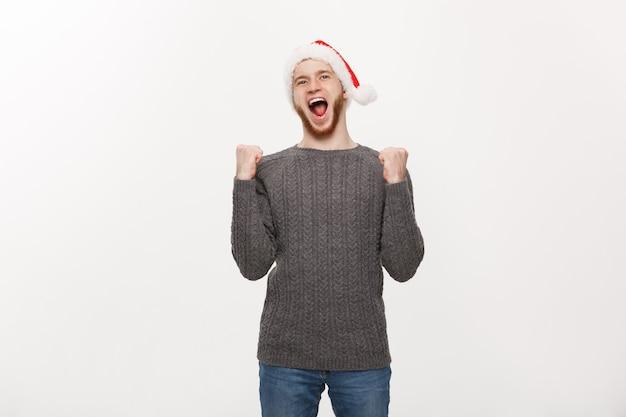 Młody człowiek z brodą w swetrze pokazuje rękę z ekscytującym uczuciem.