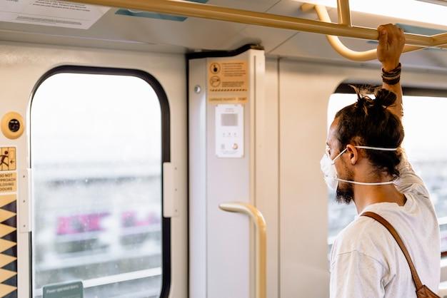 Młody człowiek z bułeczką nosi maskę w metrze