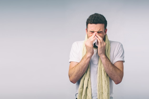 Młody człowiek z chusteczką. izolowany chory ma katar. mężczyzna leczy na przeziębienie. nerd nosi okulary.