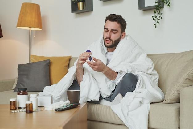 Młody człowiek z covid19 lub grypą patrząc na termometr po pomiarze temperatury, siedząc na kanapie w salonie w domu