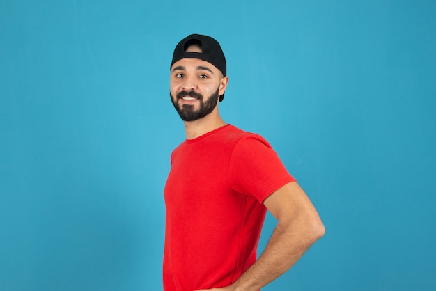 Młody człowiek z czapką na sobie czerwoną koszulkę stojącą i pozującą.