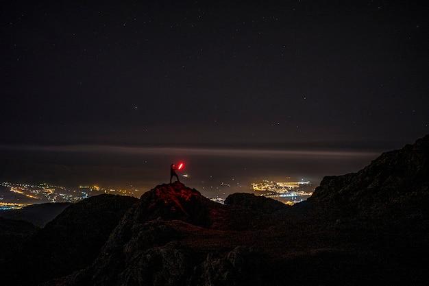 Młody człowiek z czerwonym światłem na górze aiako harria w oiartzun. kraj basków