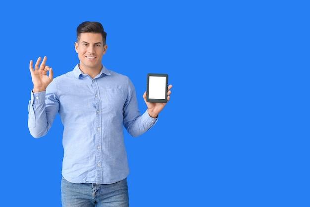Młody człowiek z czytnikiem e-booków pokazuje ok na kolorowym tle