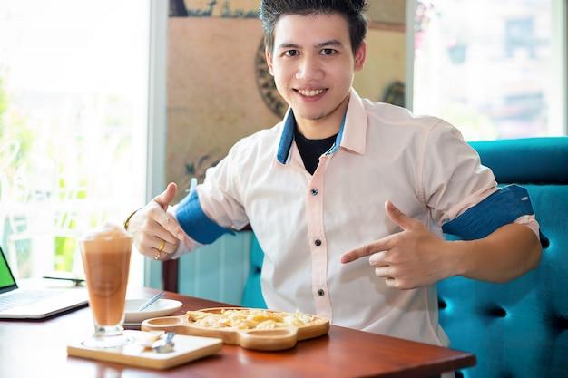 Młody człowiek z deserem w sklep z kawą