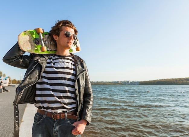 Młody człowiek z deskorolka blisko morza