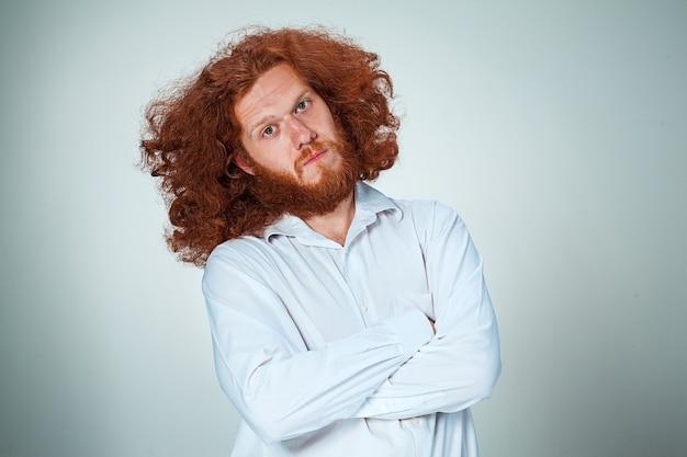 Młody człowiek z długimi rudymi włosami patrząc na kamery