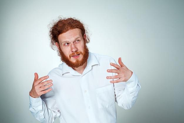 Młody człowiek z długimi rudymi włosami patrząc w kamerę, mrużąc oczy